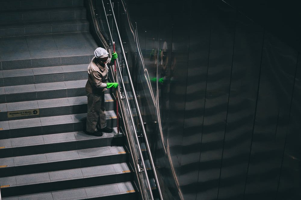 Custodian cleaning an empty stairway in a public building. Travel after coronavirus will see a new focus on hygiene and sanitation.