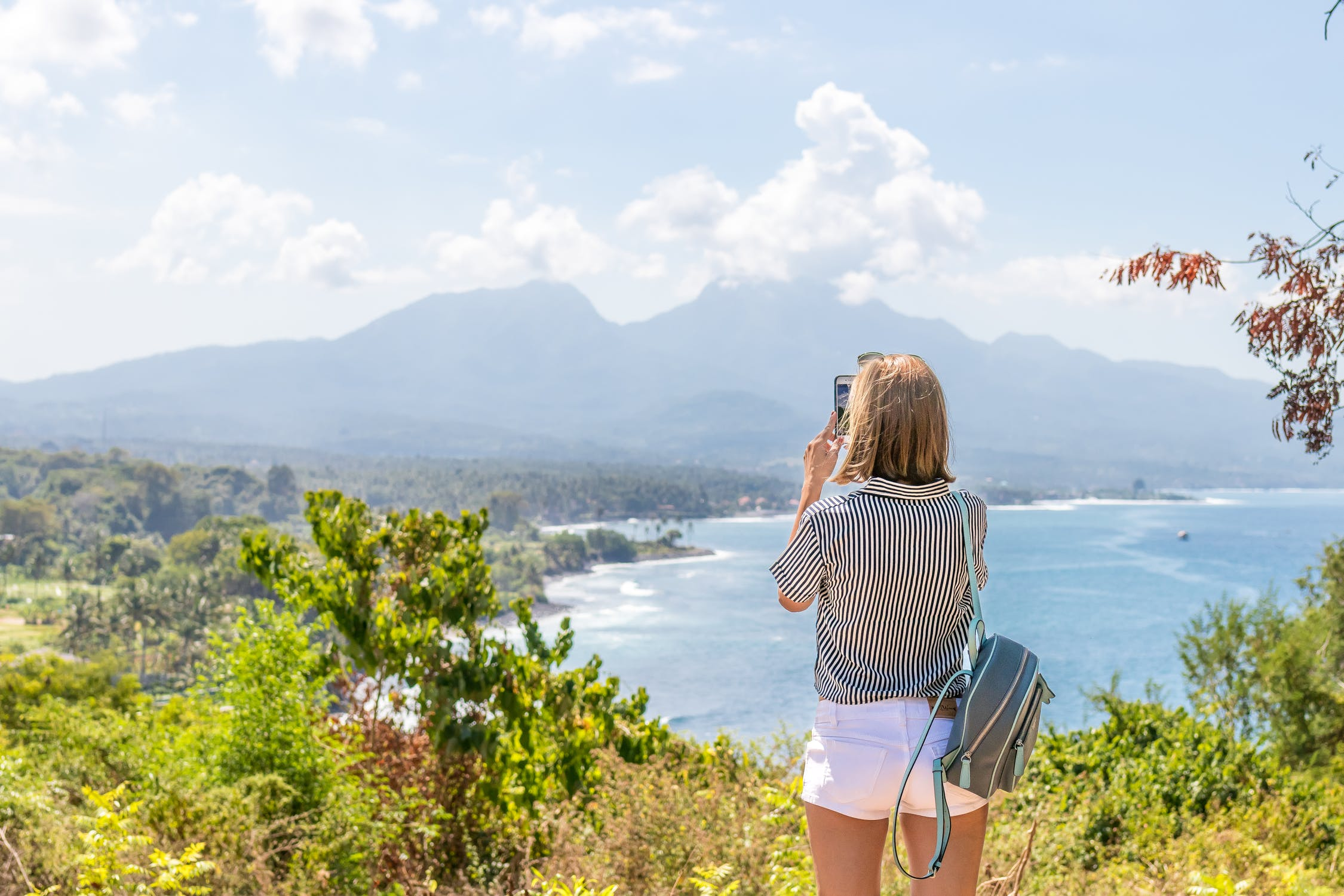 Woman taking a photo while hiking.