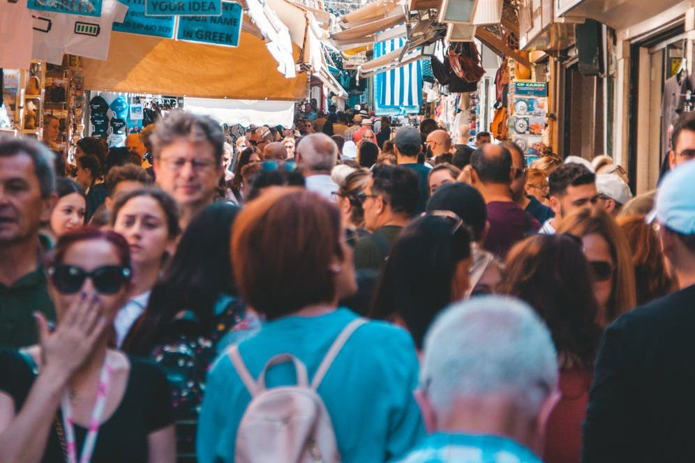 Crowded streets in a marketplace somewhere in Europe. As the industry returns to normalcy, consider your health and safety during travel after coronavirus.