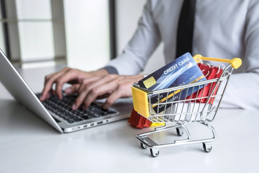 Man typing on the computer with credit cards inside of a miniature shopping cart in from