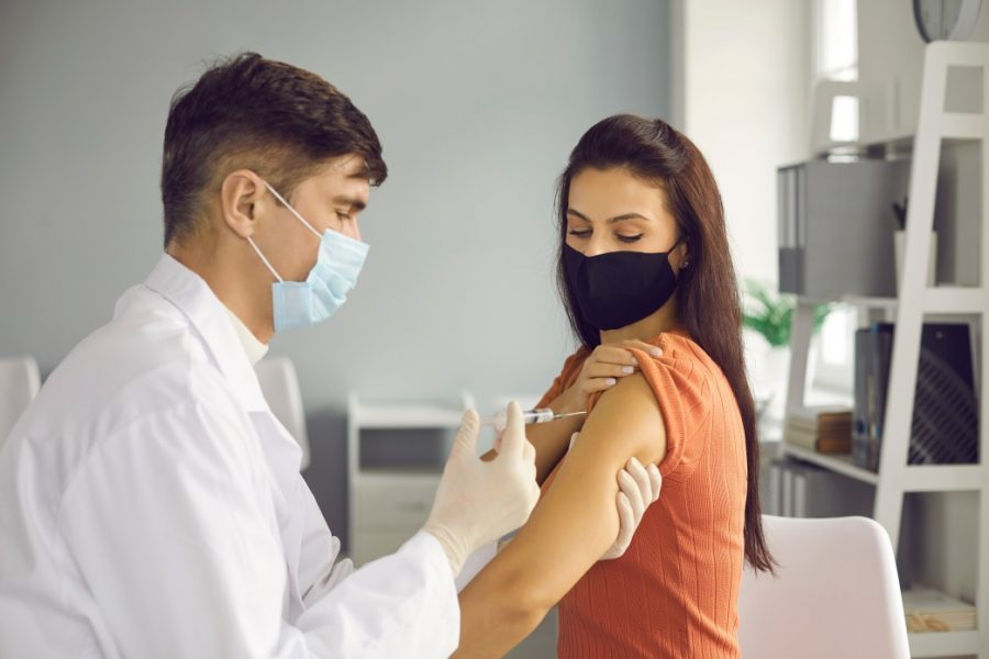 doctor holding woman's arm giving her Covid-19 vaccine in the USA