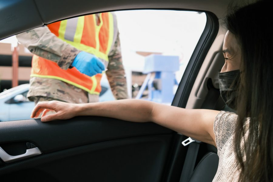 vaccine tourism in the US woman in car streching hand to get covid-19 vaccine at drive thru vaccine location